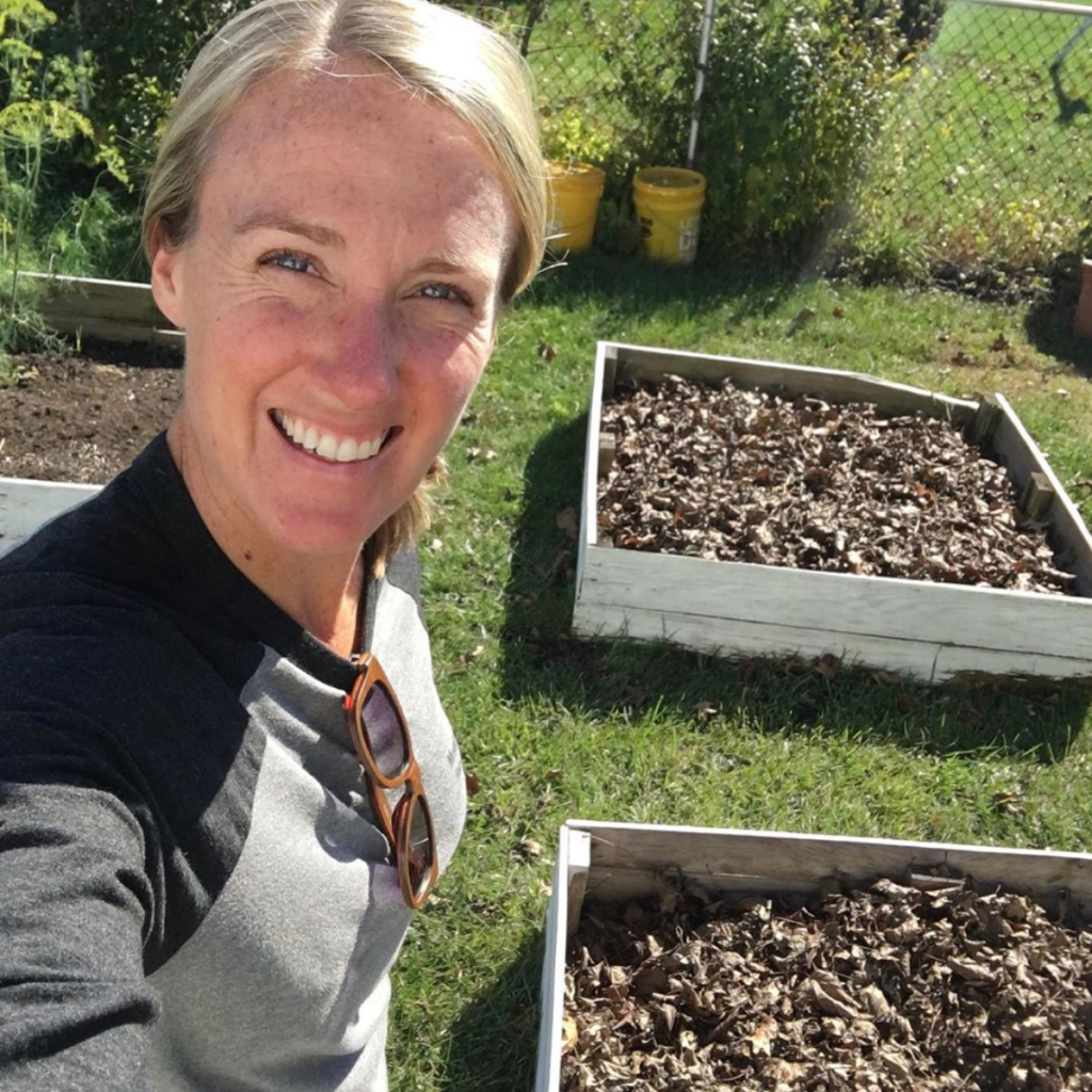 Jess is standing in front of her raised garden beds. Her blonde hair is pulled back in a bun and she is wearing a black long-sleeved shirt.