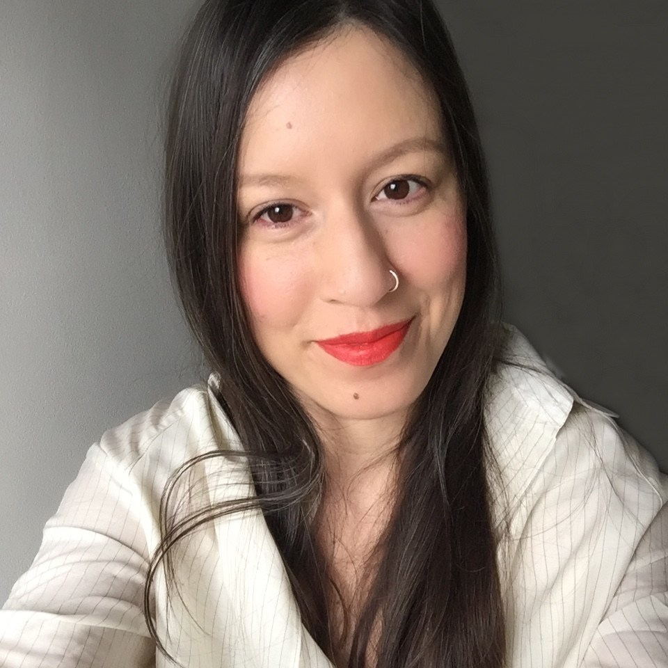 A selfie of Nash. She has long black hair and is wearing red lipstick and a white button down shirt.