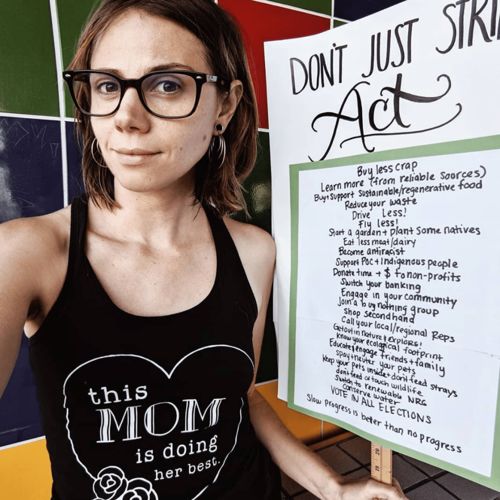 "Renate is wearing black eyeglasses and a black tank top that says ""This mom is doing her best."" She is holding a protest sign that reads ""Don't Just Strike! Act!"""