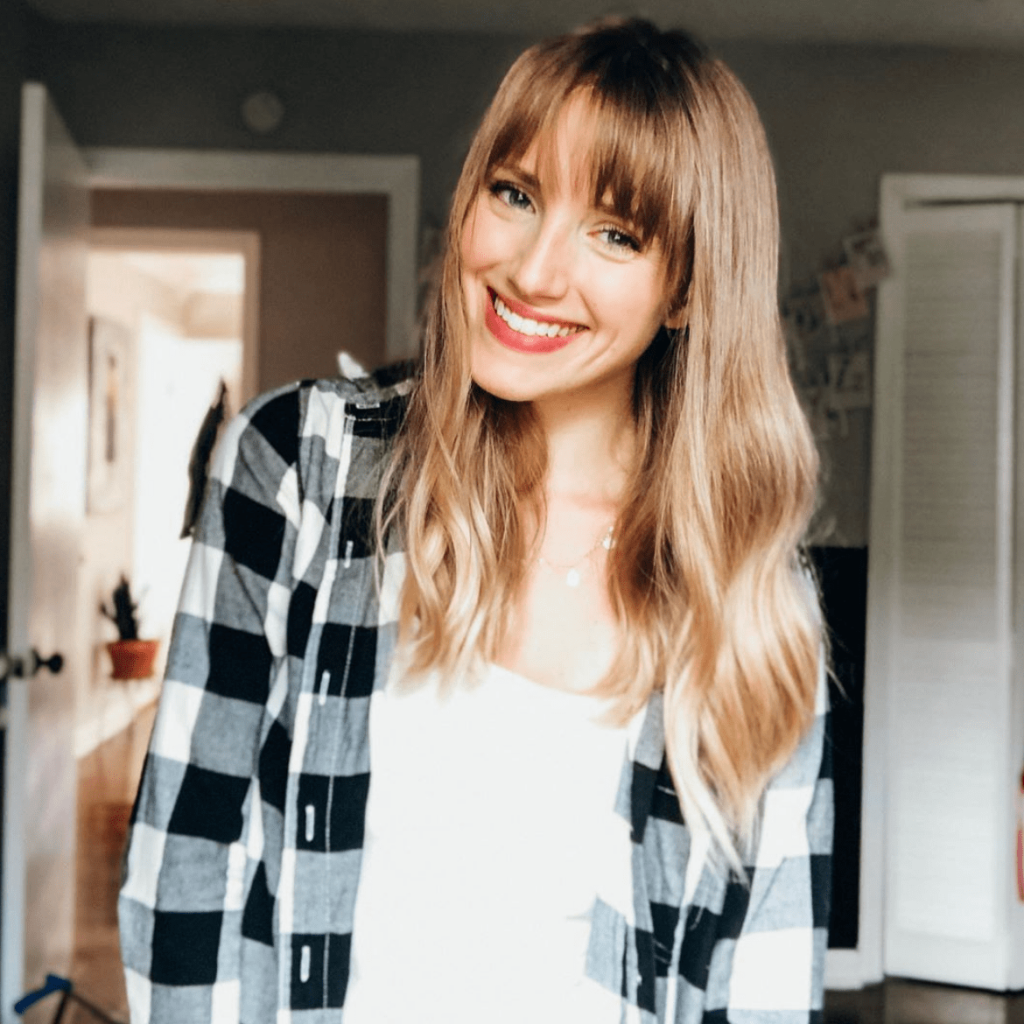 Tess has long blonde hair with bangs, and is smiling wearing a black and white checkered shirt.