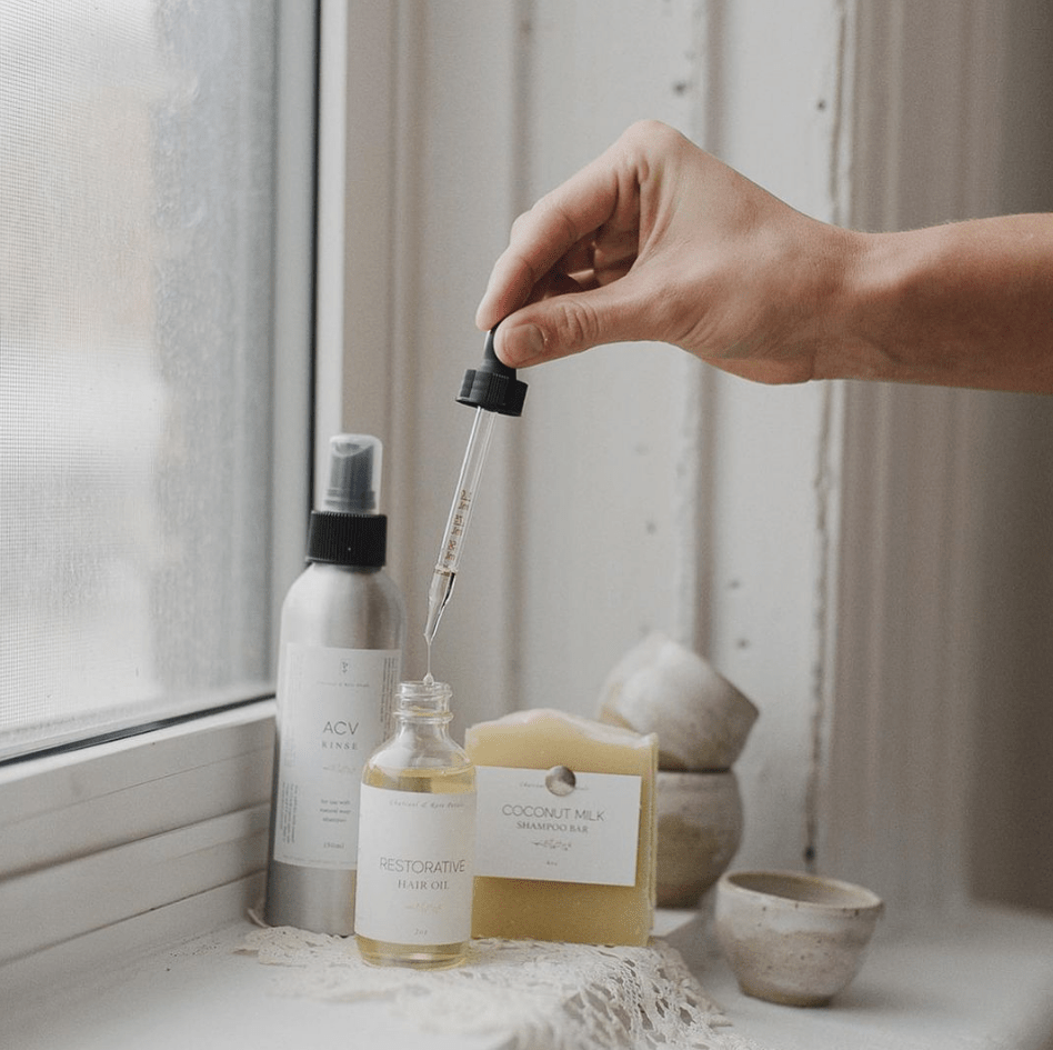 A white hand is on the right side of the frame, holding an eye dropper above a bottle of oil. To the left is a metal spray bottle, and to the right is yellow/beige bar of soap. Behind these sit a few small pottery bowls. Everything sits on a white windowsill.