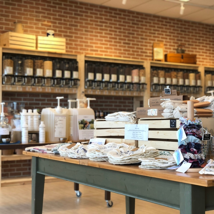 Photo of Earth Market store in Newmarket ON. Smaller products and refill containers with pumps sit on two tables in the foreground. In the background are several shelves with more products and glass jars.