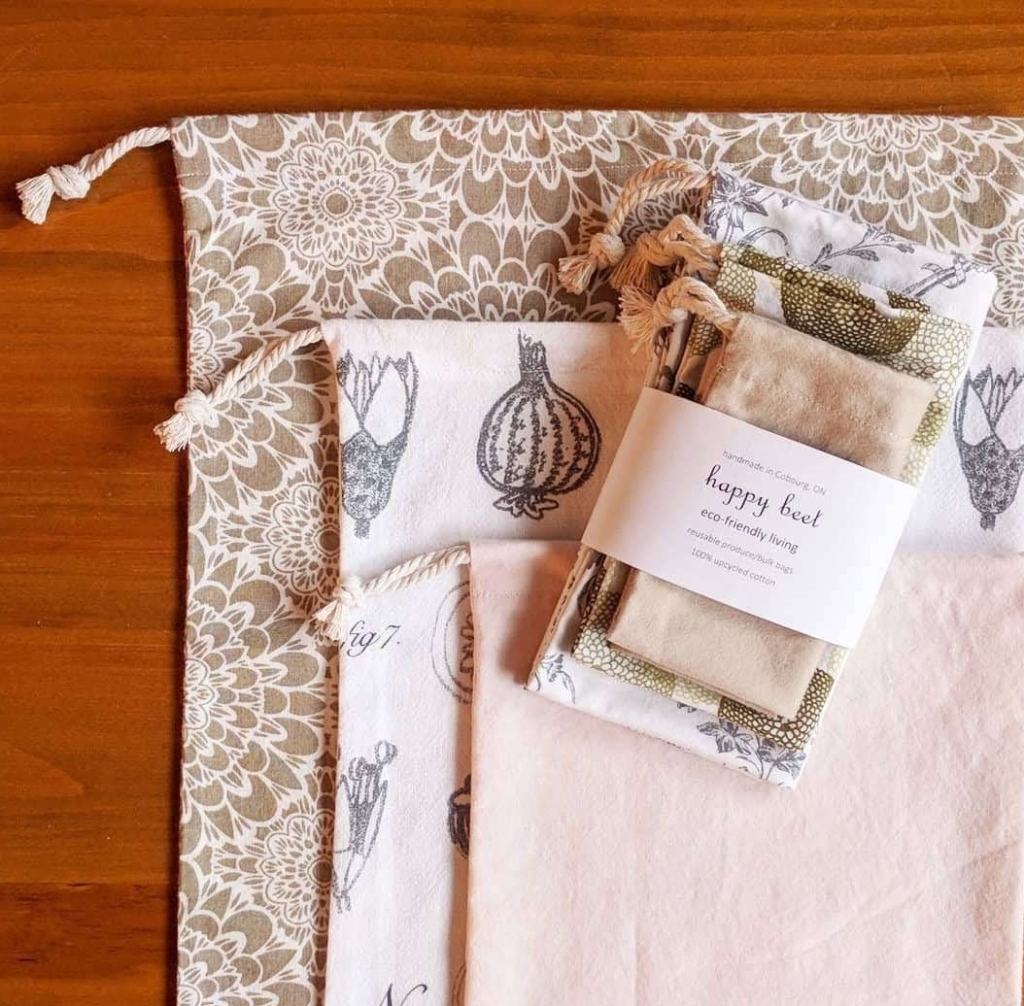 A flat lay of three cloth produce bags, with a set of three bags banded in the Happy Beet label on top. The largest bag is brown with white flowers, the medium bag is white with a black floral print, and the smallest bag is light pink.
