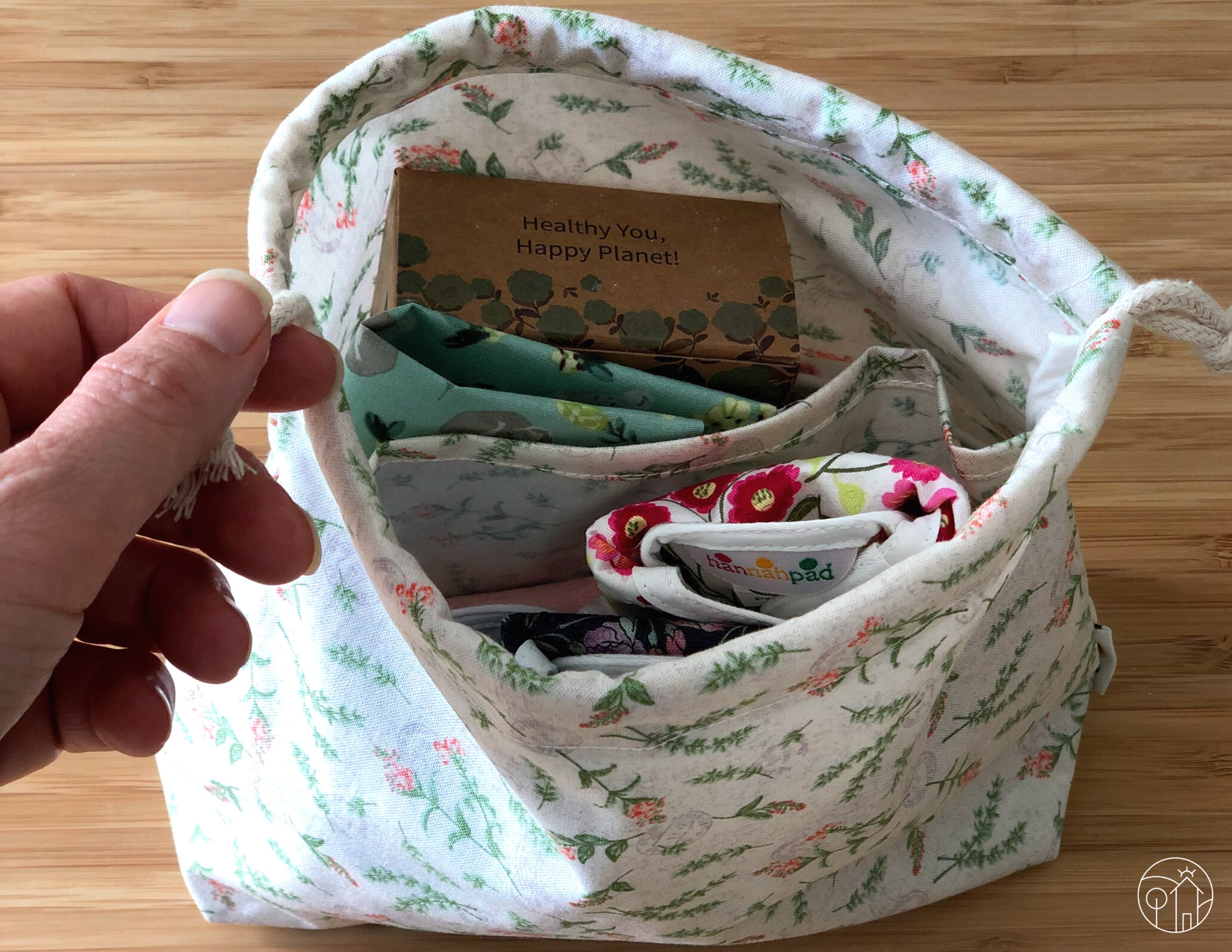Overhead view of a wet bag, containing several cloth pads in various floral prints.